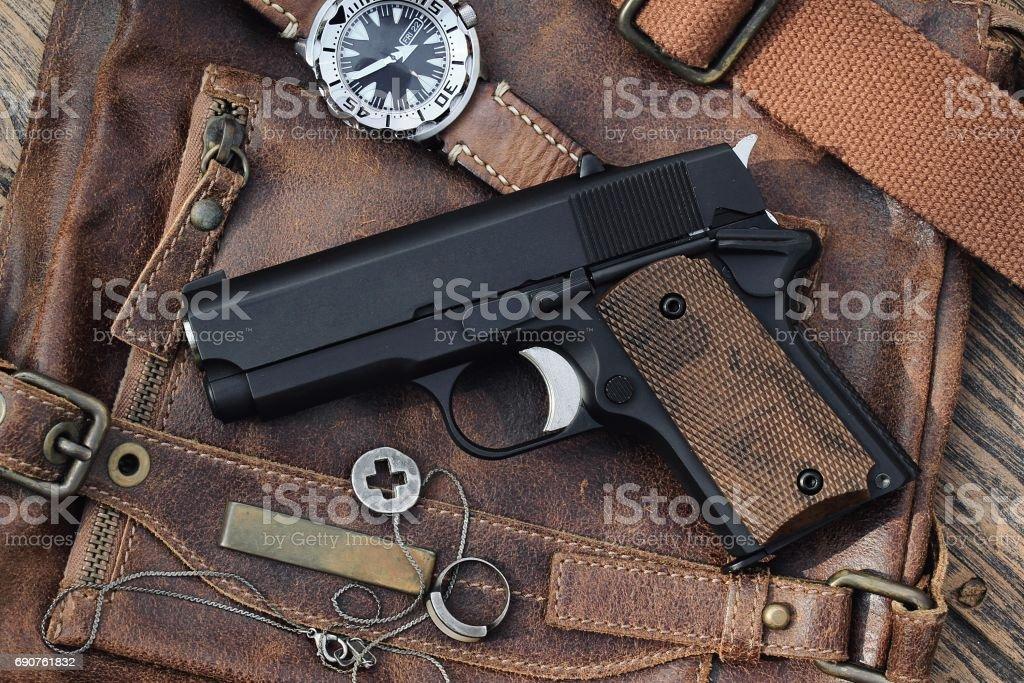 Small black gun (compact handgun) lying over a Leather handbag, .45 pistol. stock photo