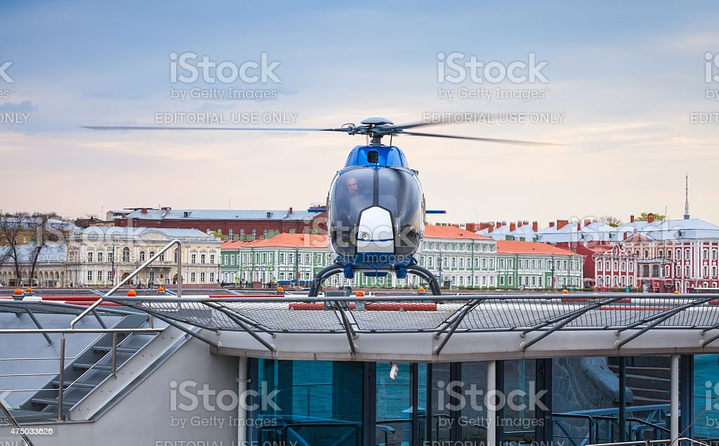 Small blue helicopter stands on the floating helipad stock photo
