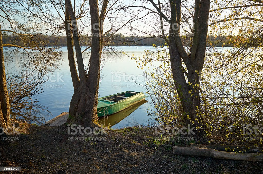 Small boat and pier near shore lake.  reflection water stock photo