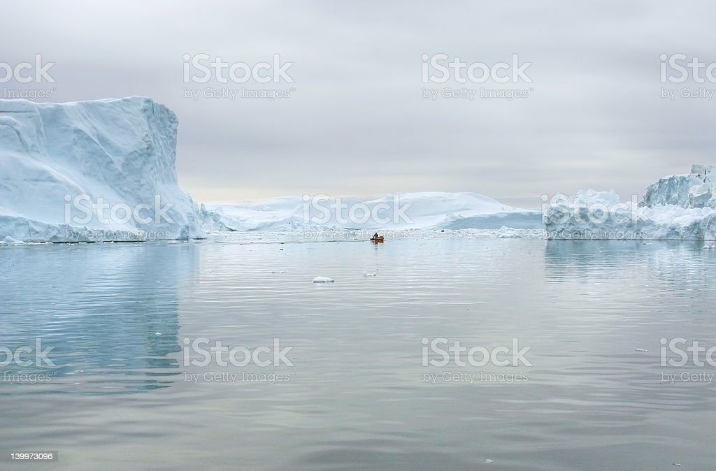 Small boat between icebergs, Greenland stock photo