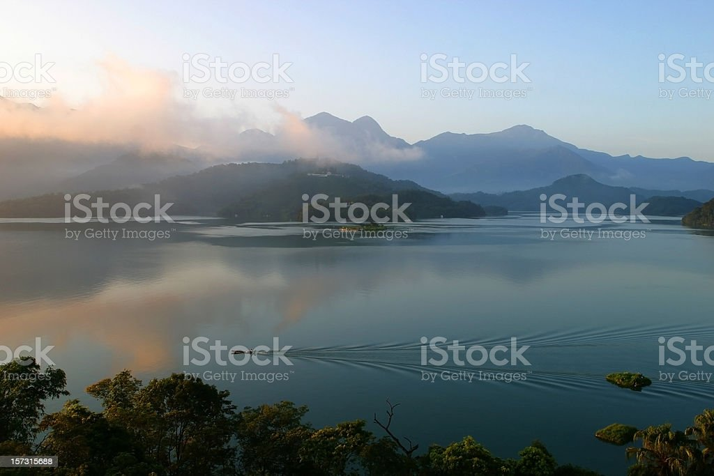 Small Boat Gliding Through a Tranquil Lake stock photo