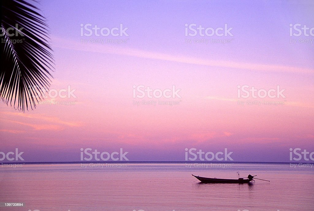 A small boat in calm water at purple sunset royalty-free stock photo