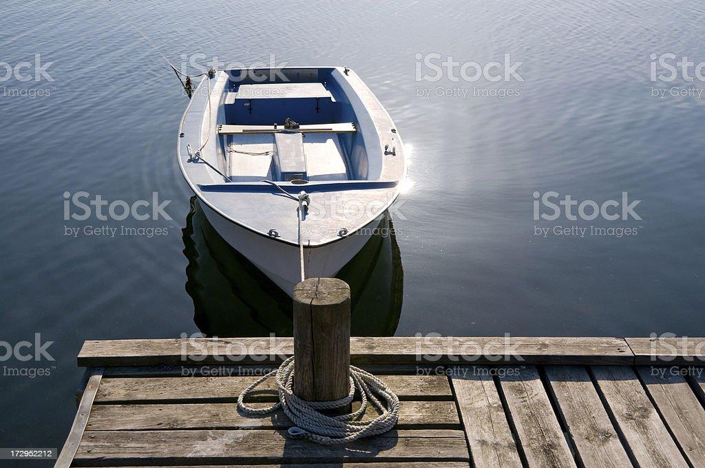 Small boat moored, sunlight reflection royalty-free stock photo