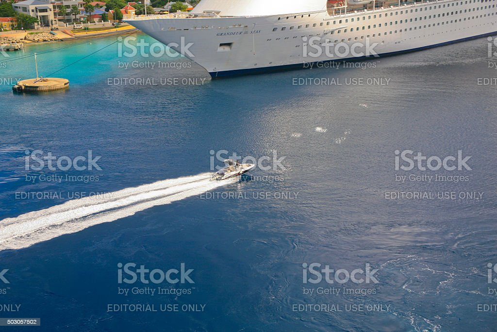 Small Boat Speeding Past a Huge Cruise Ship stock photo