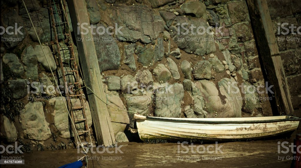 small boat tie in in muddy water stock photo