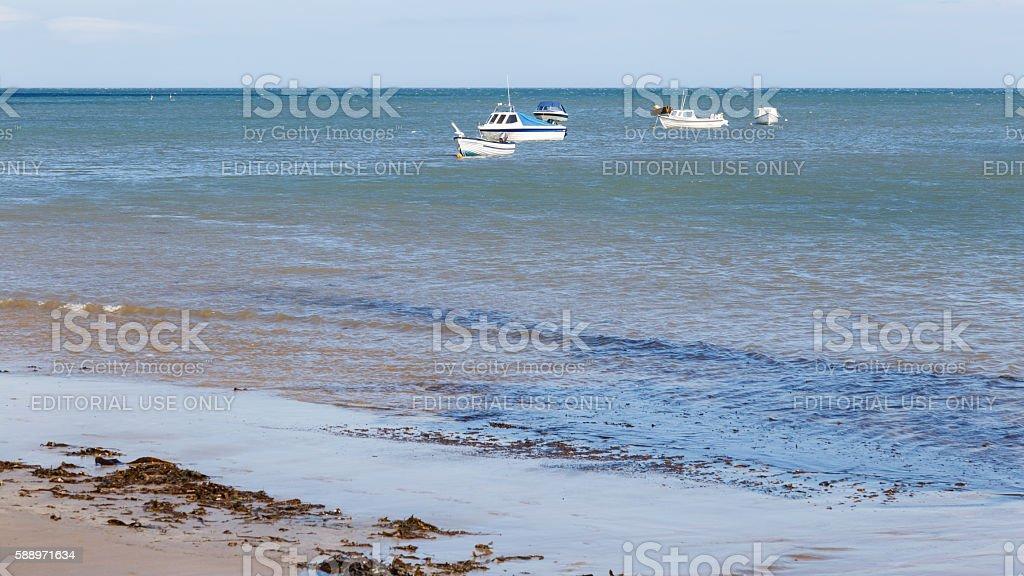 Small boats anchored off shore stock photo