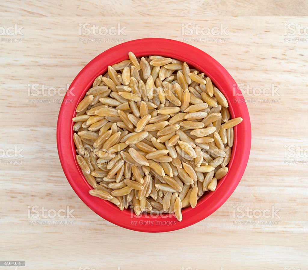 Small bowl filled with Khorasan wheat on table top view stock photo