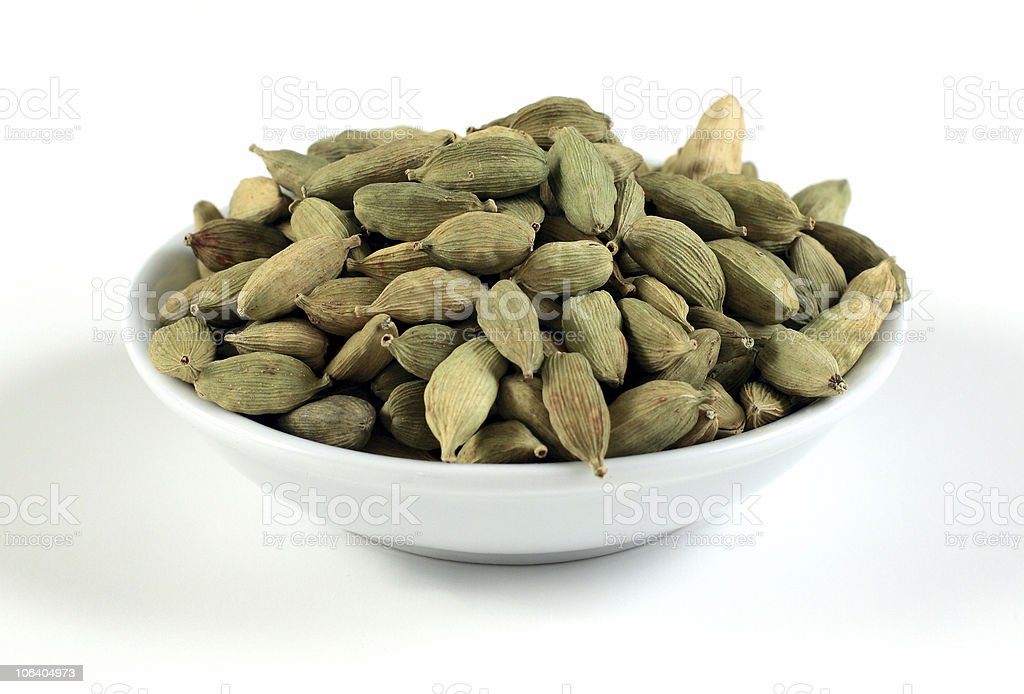 Small bowl of green cardamom pods stock photo
