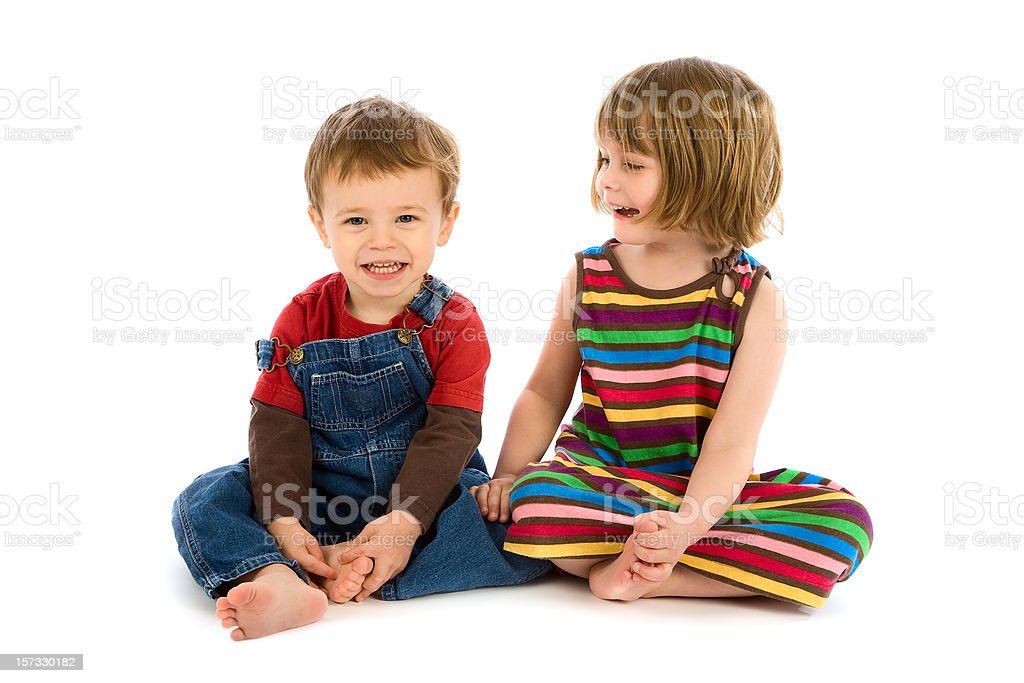 Small boy and girl sitting together smiling on white royalty-free stock photo