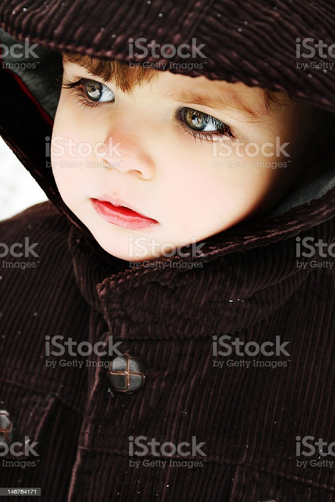 Small boy bundled up in winter coat and hat stock photo