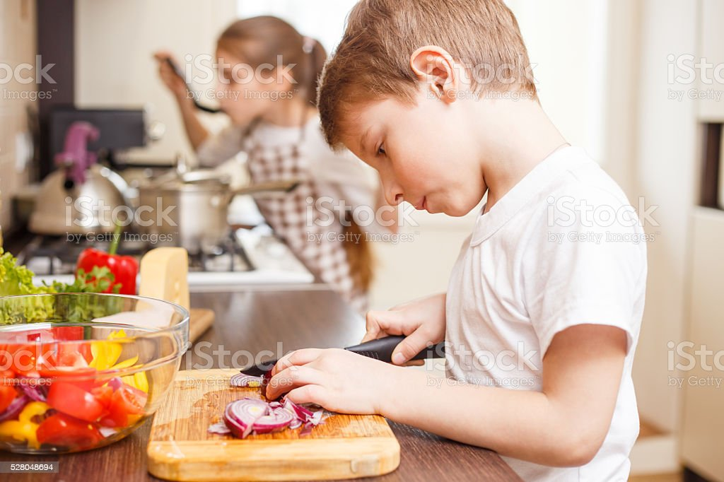 Small boy cooking together with his sister stock photo