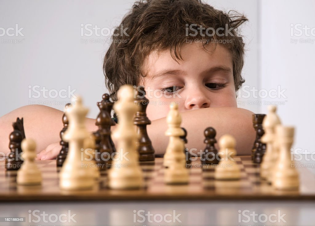 Small boy deep in thought as he contemplates his chess move royalty-free stock photo