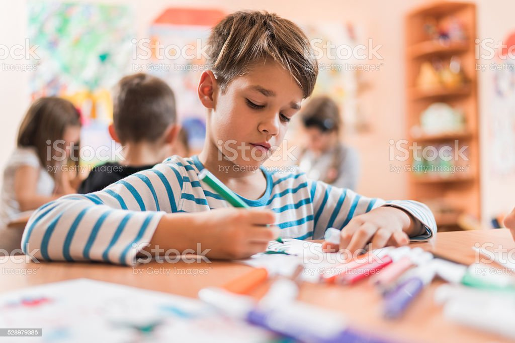 Small boy drawing on a class in a preschool. stock photo