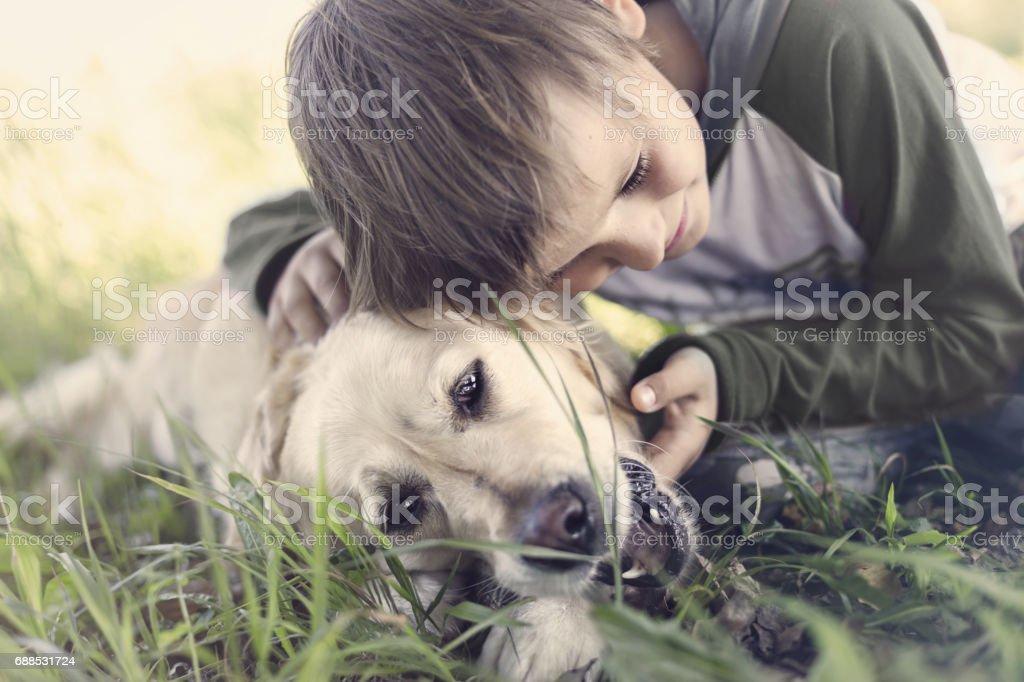 Small boy embracing sweetly his dog stock photo