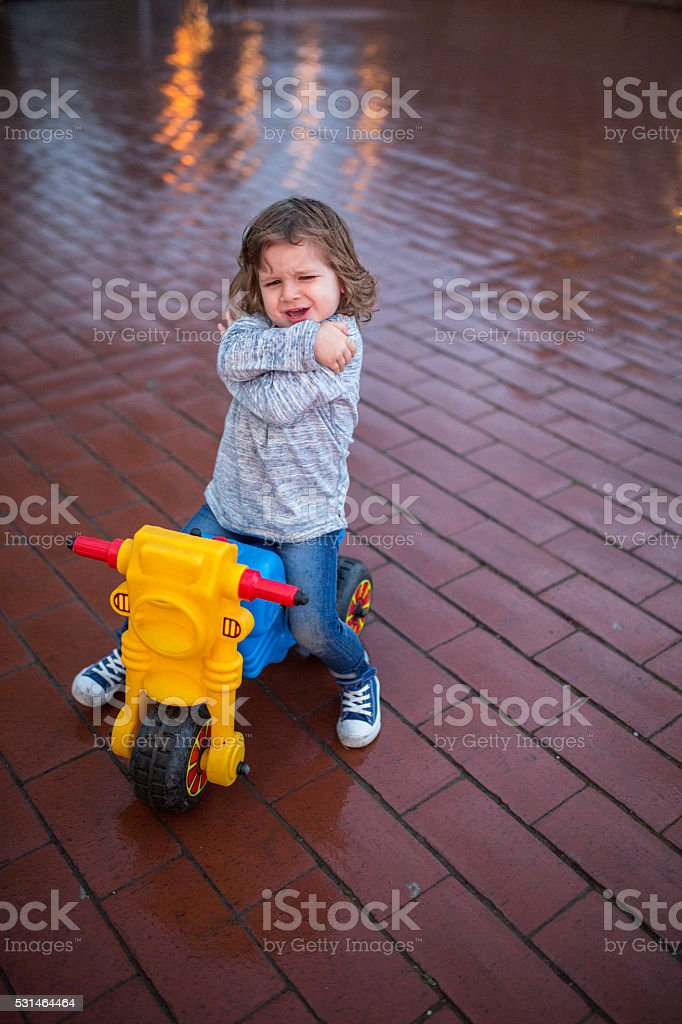 Small boy frowning on toy motorcycle with arms crossed. stock photo