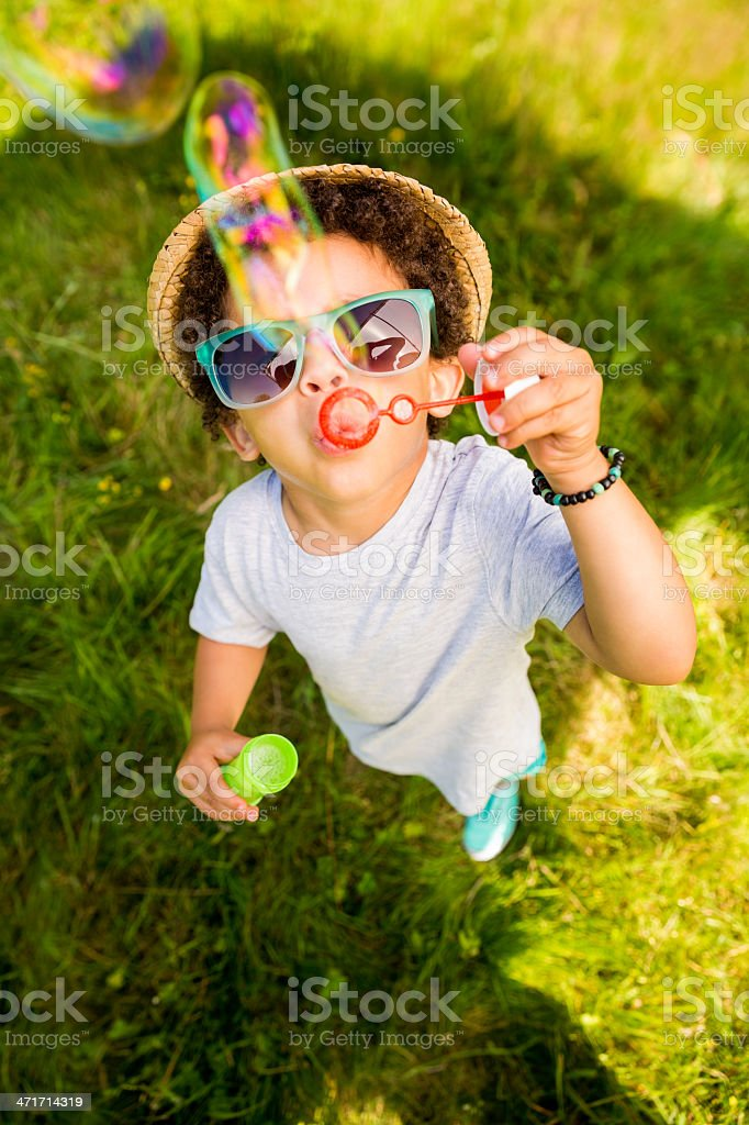 Small boy having fun blowing bubbles stock photo