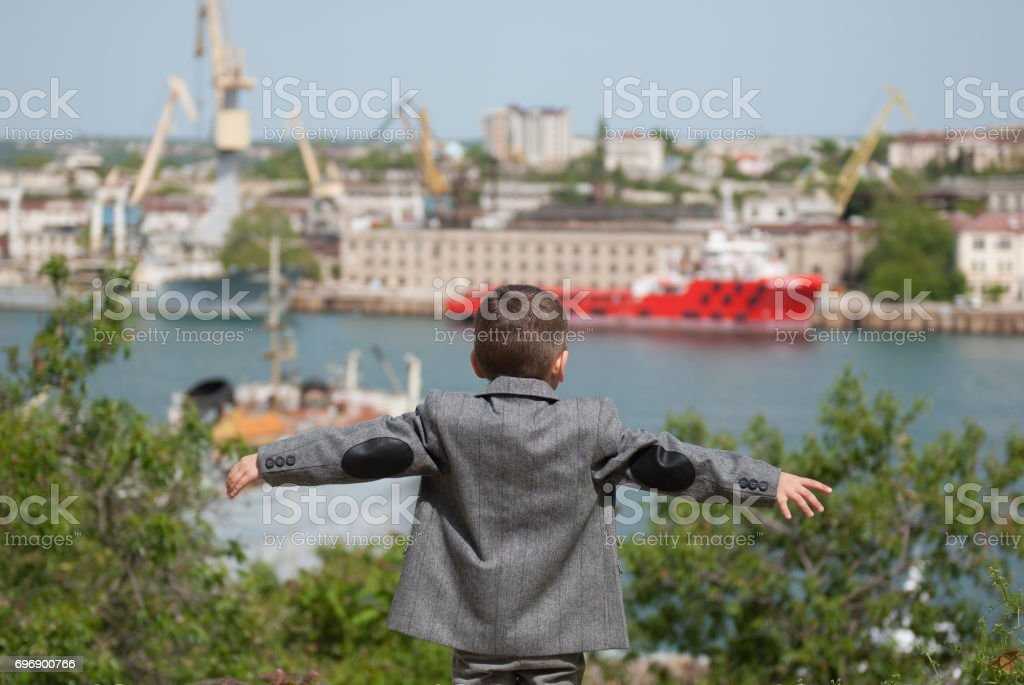 small boy in a jacket stands against the backdrop of a seaport with his hands outstretched stock photo