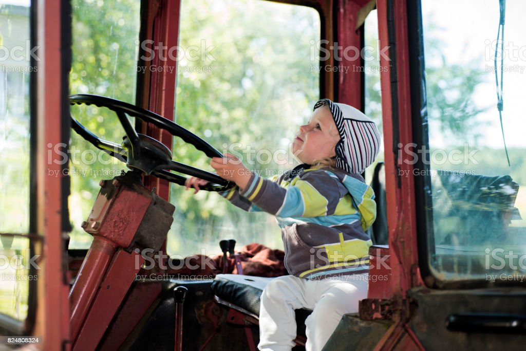 Small boy in old red Tractor. stock photo