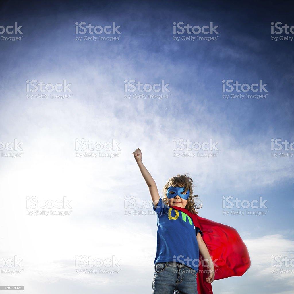 Small boy in superhero attire against blue sky stock photo