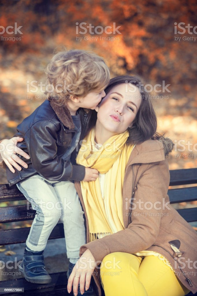 Small boy kissing his mother. stock photo