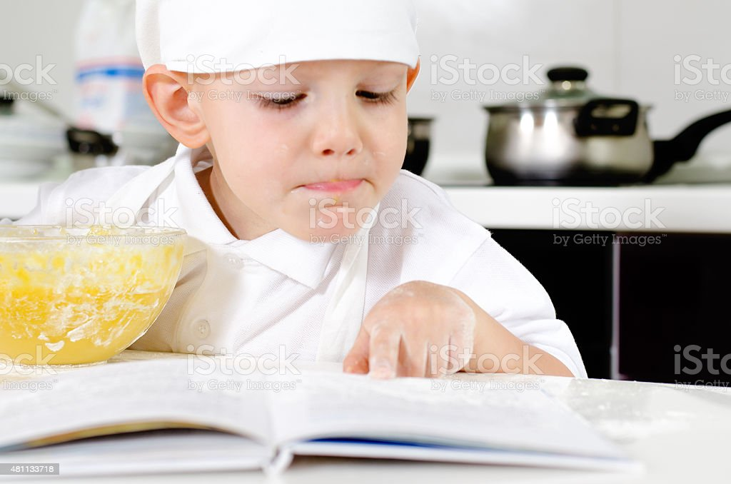 Small boy learning to cook checking his mixture stock photo