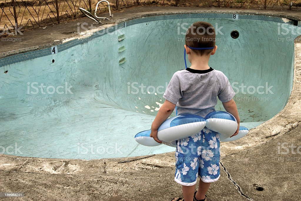 Small Boy Looking at Empty Pool stock photo