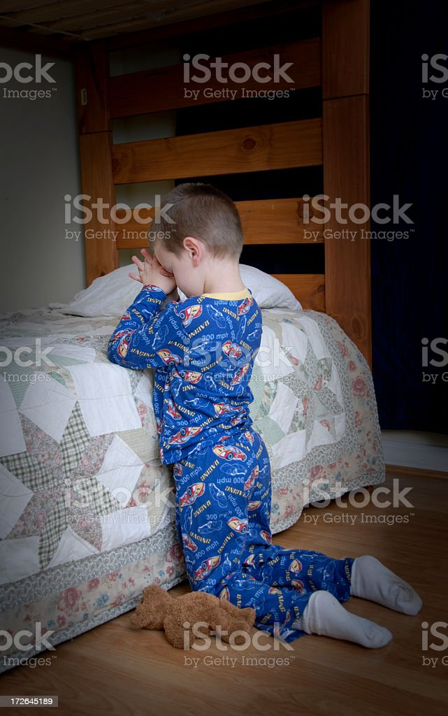 Small boy making his bedtime prayers stock photo