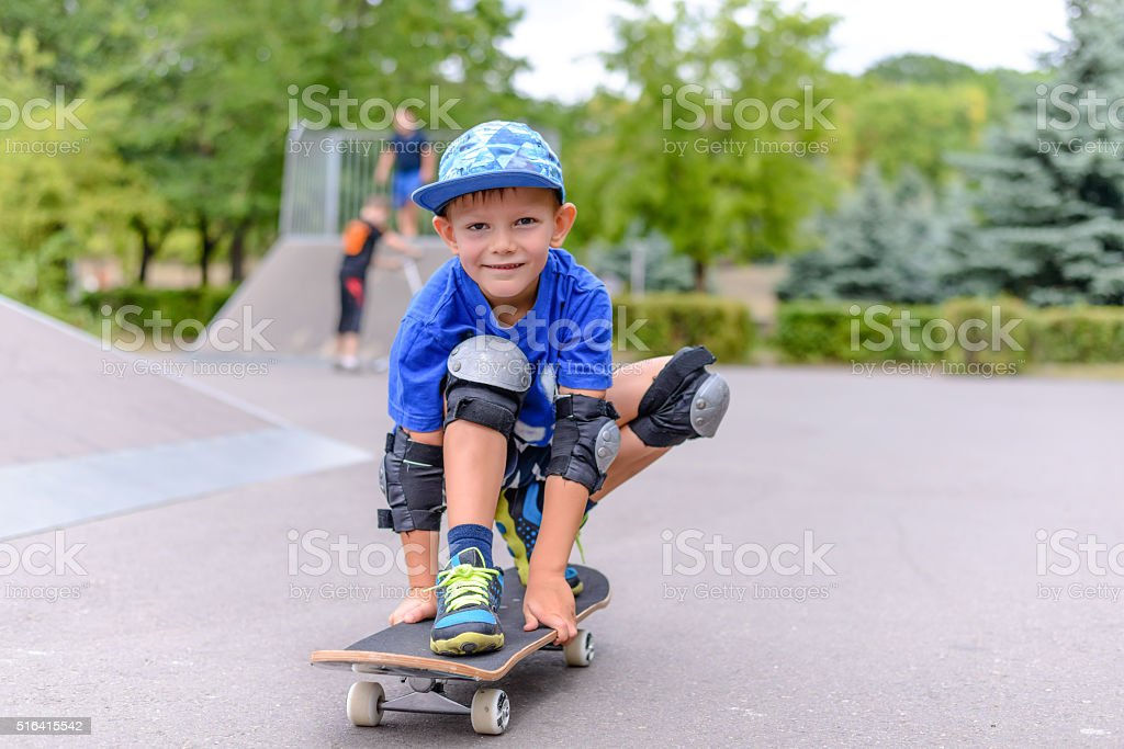 Small boy on his skateboard grinning at the camera stock photo