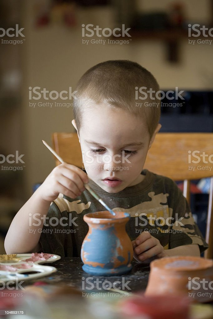 small boy paints the clay jar royalty-free stock photo