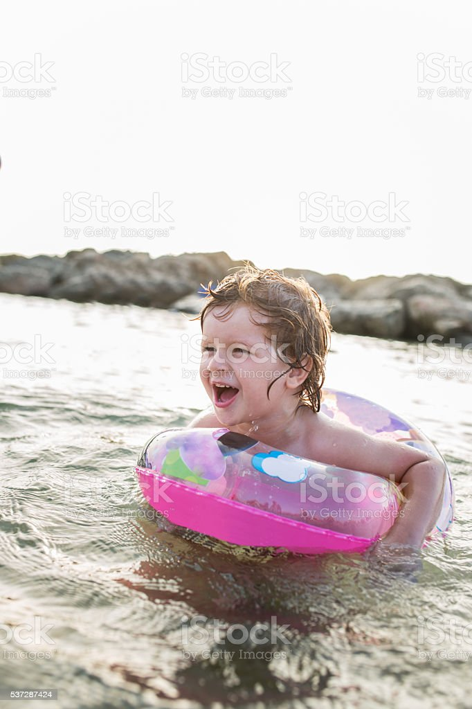 Small boy screaming in a swimming tube at sea. stock photo
