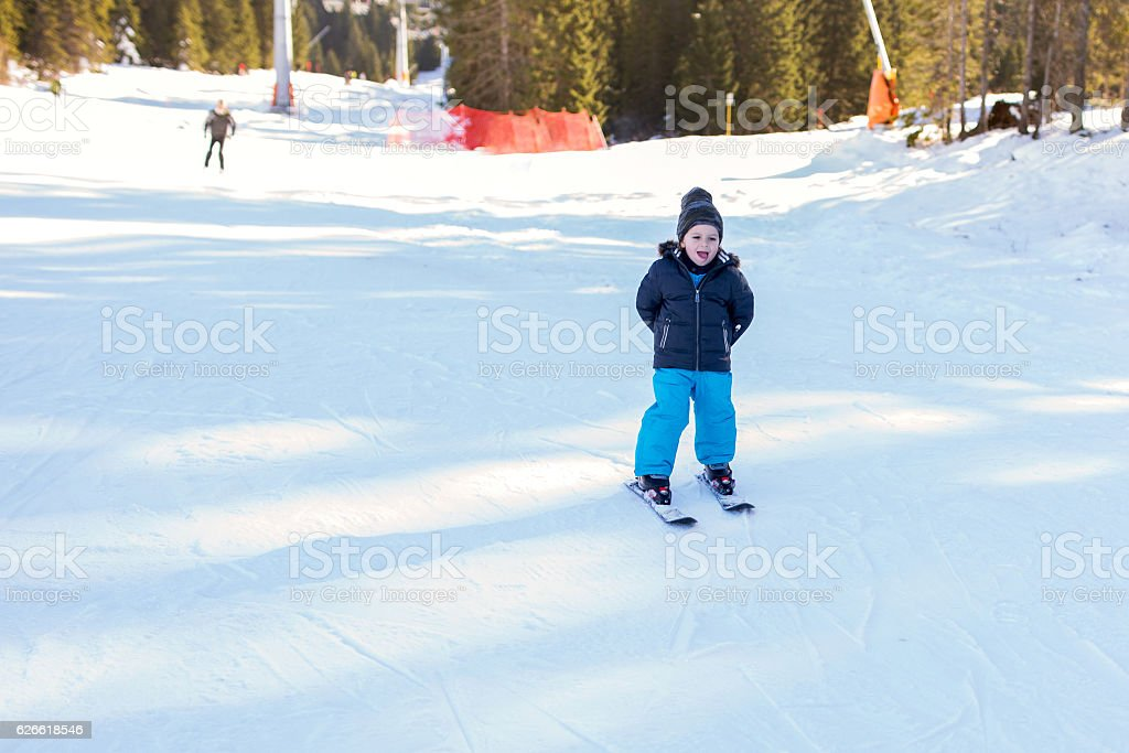 Small boy skiing with hands behind back. stock photo