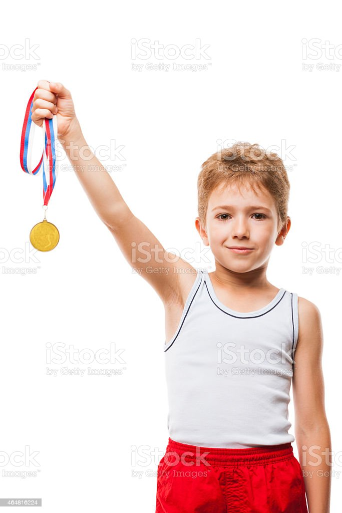 A small boy smiling and holding up his winning medal stock photo