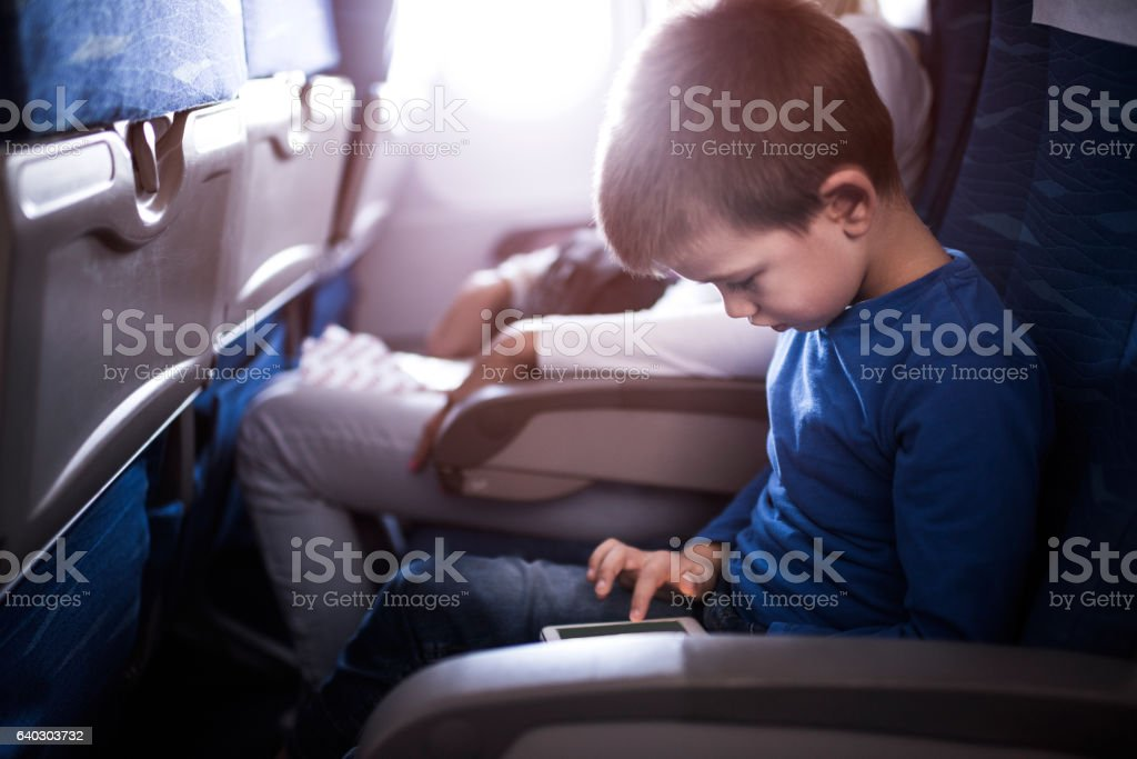 Small boy using cell phone while traveling by plane. stock photo