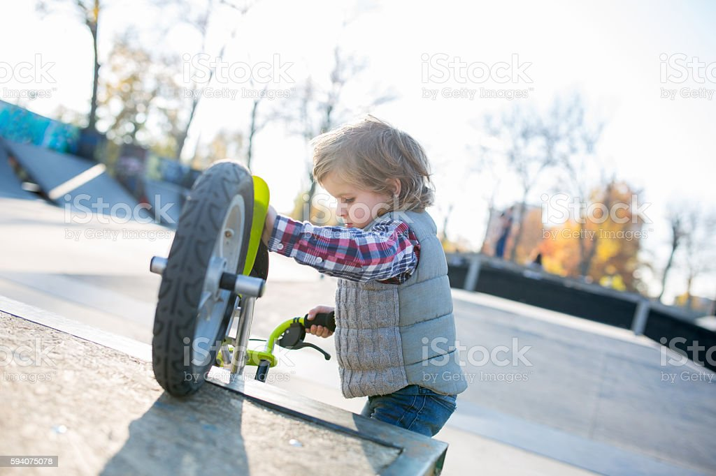 Small boy with bike in skate park. stock photo