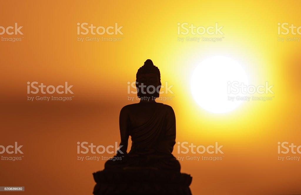 small buddha figurine meditating in sunlight - sunset stock photo