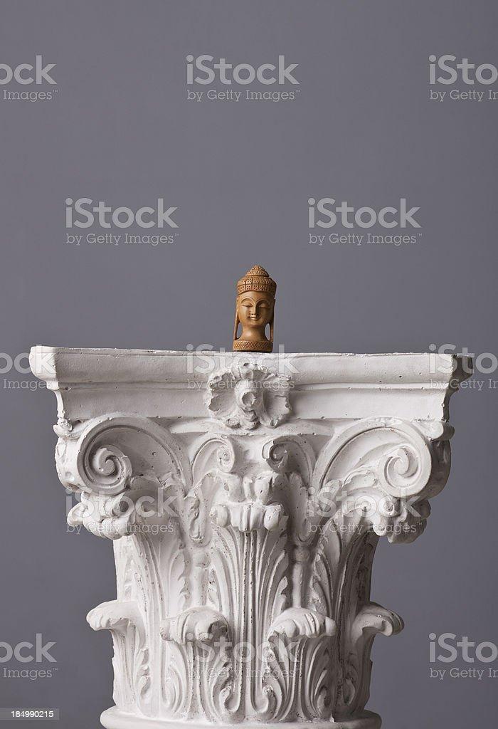 small buddha statue on a corinthian capital stock photo