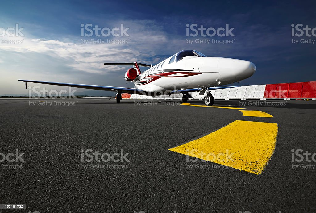 A small business jet on a runway from a ground view stock photo