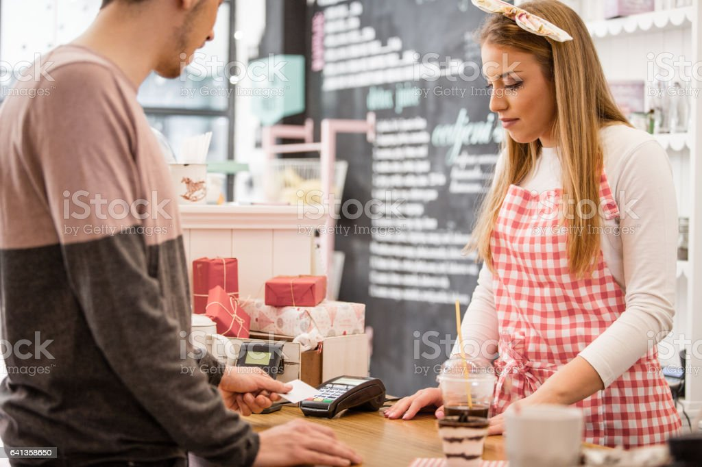 Small business owner accepting payment with contactless credit card reader stock photo