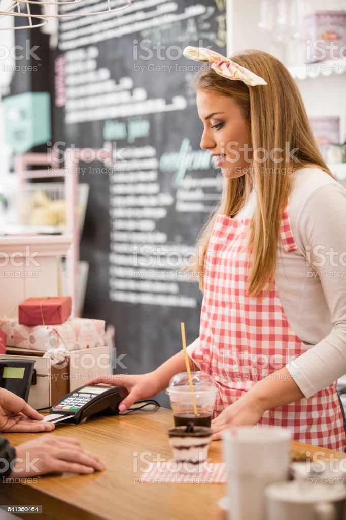 Small business owner accepting payment with credit card reader stock photo