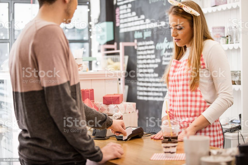 Small business owner accepting payment with slip credit card reader stock photo