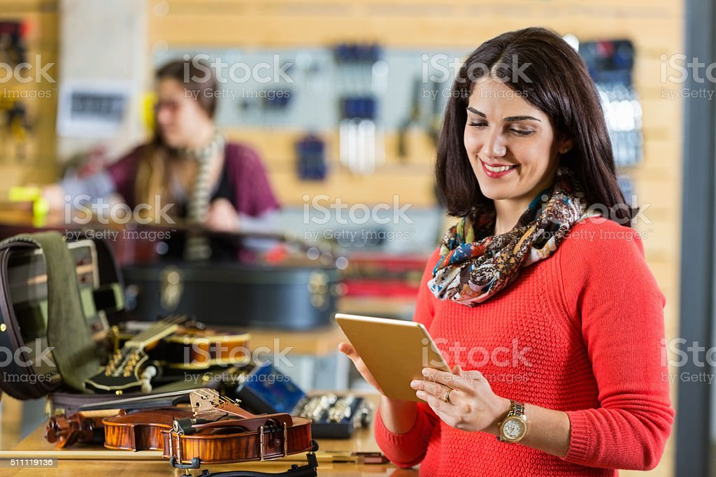 Small business owner checking customer orders for musical instruments stock photo