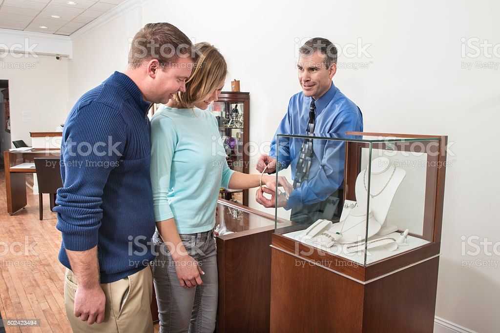 Small Business Owner Helping Happy Couple Shop for Jewelry stock photo