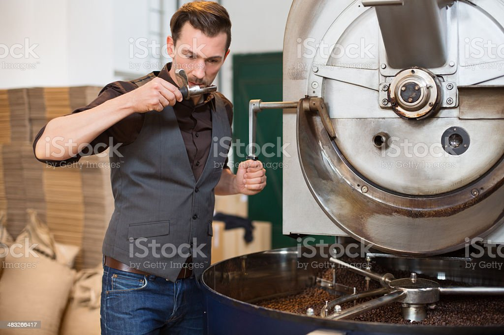 Small business owner smelling a scoop of roasted coffee stock photo
