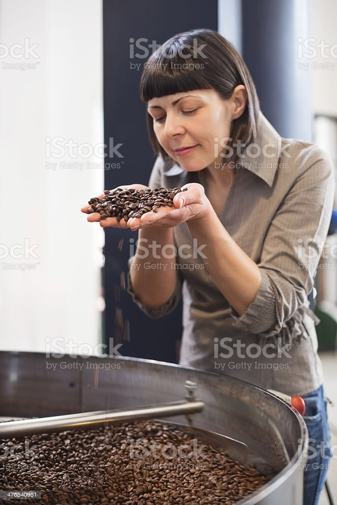 Small business owner smelling fresh roasted coffee royalty-free stock photo