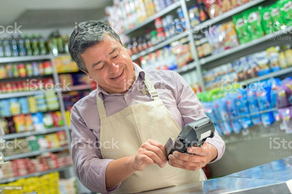 Small business owner using a credit card reader stock photo