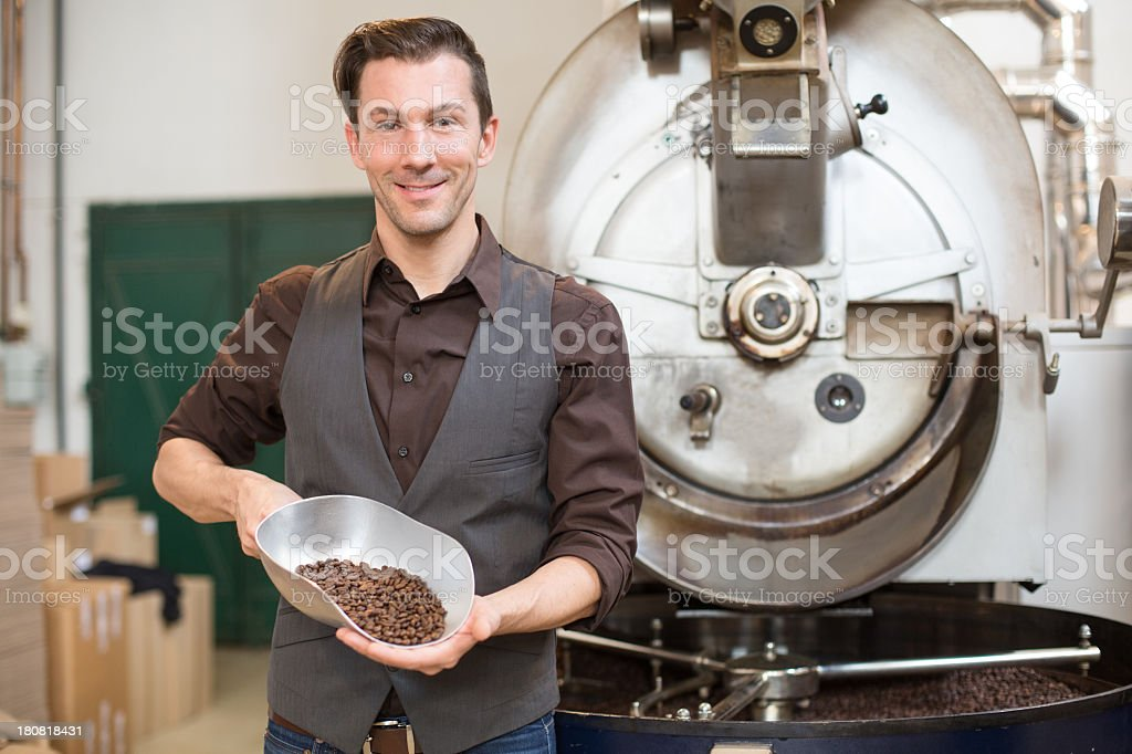 Small business owner with a scoop of roasted coffee royalty-free stock photo