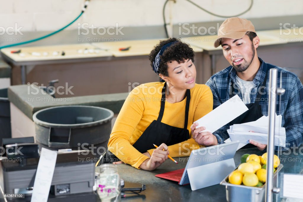 Small business owners, paying bills stock photo