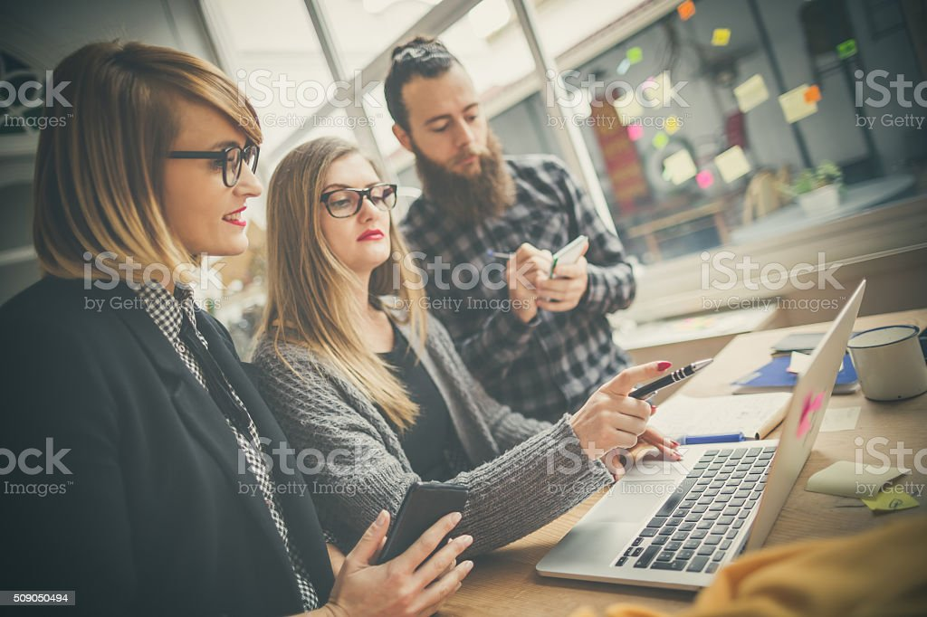 Small business start up team: briefing on laptop stock photo