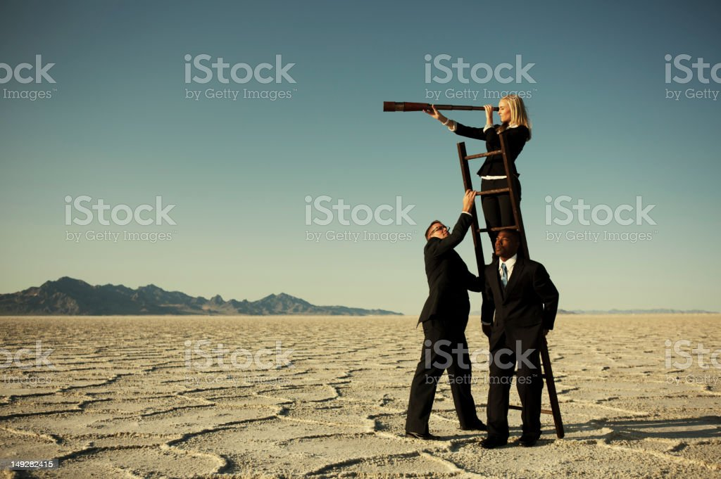 Small Business Team Search through Telescope on Salt Flats stock photo