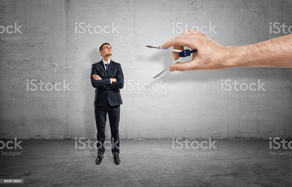 Small businessman on concrete background being measured by giant hand stock photo